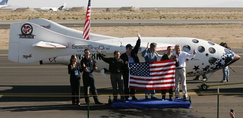 SpaceShipOne and X Prize team members pose with a U.S. flag carried aboard the spacecraft after its successful flight into space and landing at Mojave, Calif., Airport Monday, Oct. 4, 2004.
