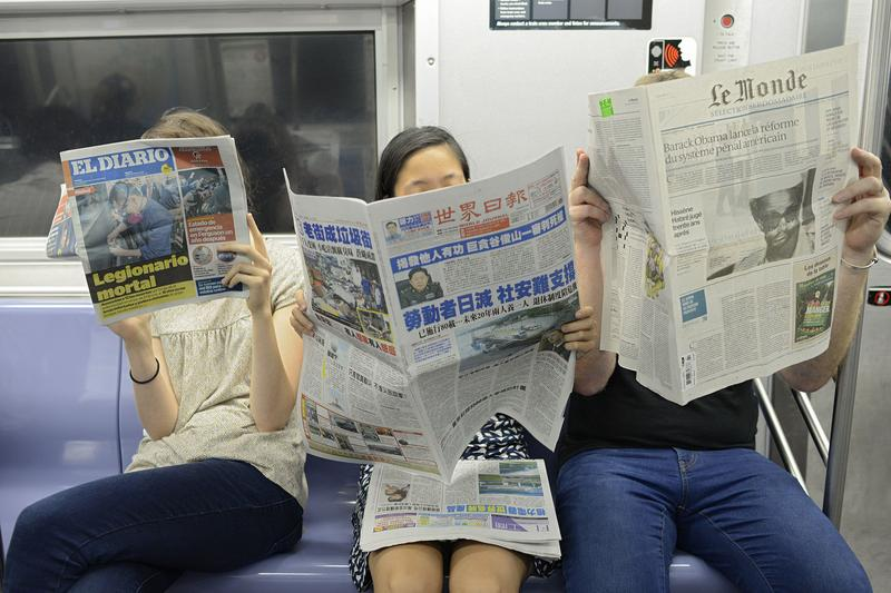 People on Subway Reading Spanish, Chinese and French Newspapers