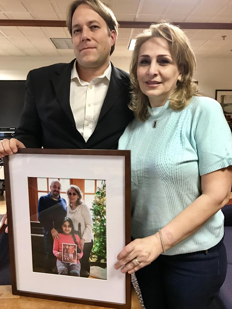 Pastor Seth Kapper-Dale of the Reformed Church of Highland Park with Najla, of Syria, who is living here seeking asylum. They are posing with a picture of her family.