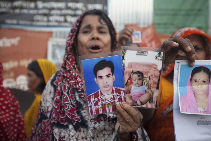 Relatives of the victims of the April 24 Rana Plaza building collapse display photographs of their dear ones as they gather to pay tributes at the venue of the tragedy at Savar, outskirts of Dhaka.