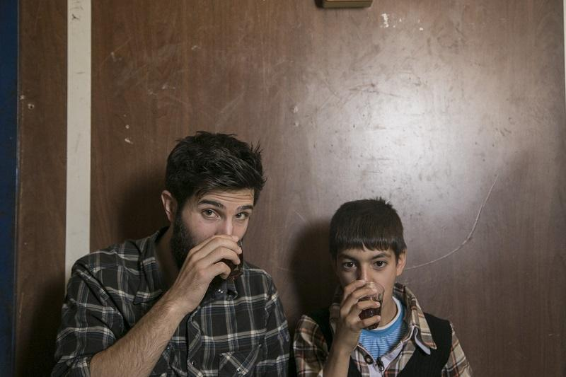 "Zach Ingrasci, filmmaker, and Raouf sipping tea in the film, ""Salam Neighbor."""