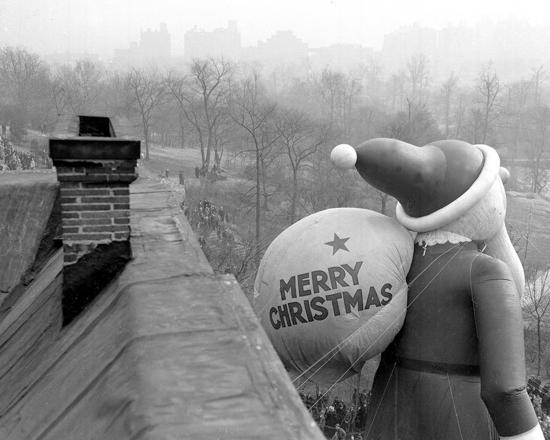 Santa Claus climbs down Central Park West while one of chimneys he'll come down Christmas Eve, stands in foreground.