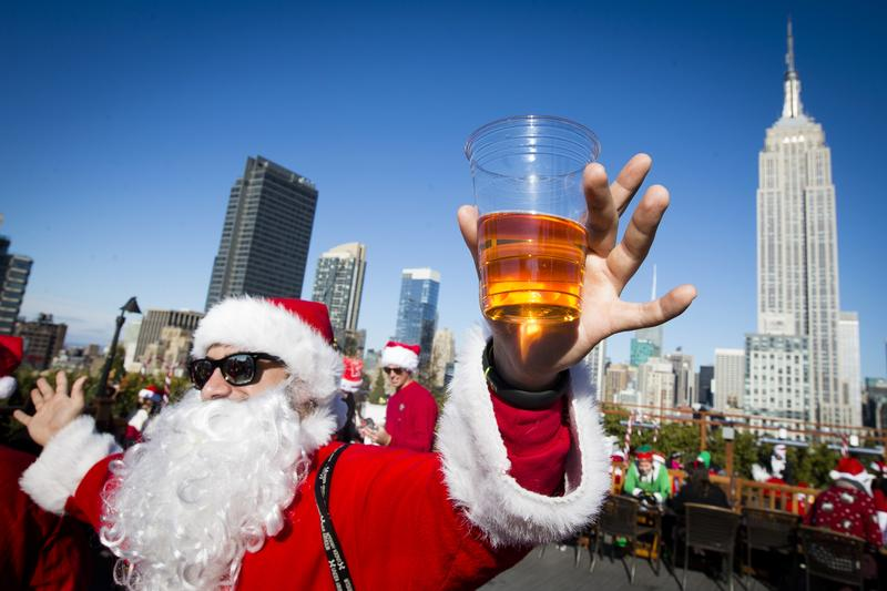 A man dressed as Santa Claus holds a beer as he and others participate in SantaCon on a rooftop bar Saturday, Dec. 13, 2014, in New York.