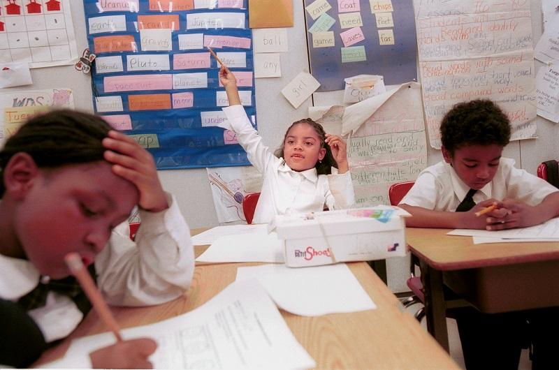 Tasia Burroughs of Sisulu Children''s Adademy, a Harlem charter school, raises her hand during class Jun 21, 2000 in New York City.