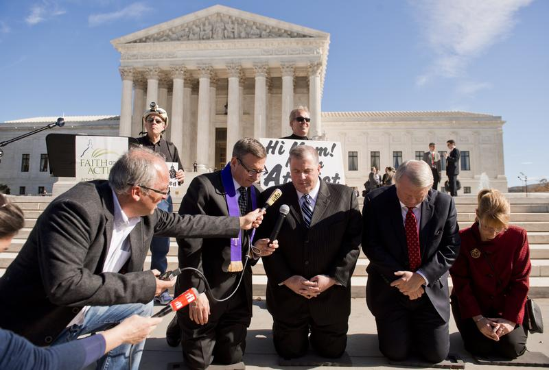 Religious activists pray following oral arguments in the case of Town of Greece v. Galloway dealing with prayer in government, outside the Supreme Court.