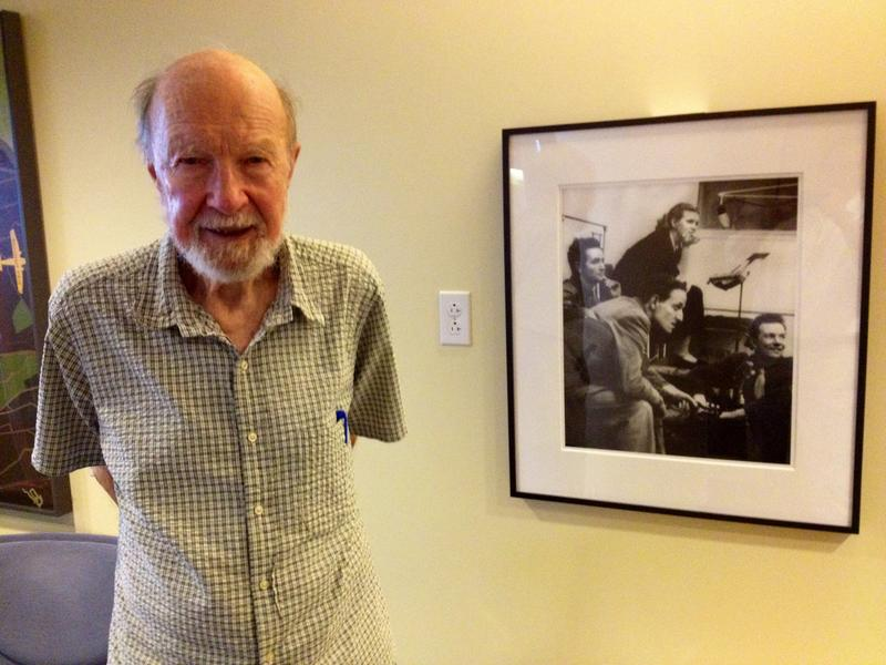 Pete Seeger at WNYC in 2012, next to a picture of himself at WNYC in 1941