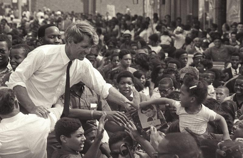 American senator Robert F. Kennedy (1925 - 1968) stands in an open-top convertible and shakes hands with members of a crowd as he campaigns for the democratic Presidential nomination in Detroit.