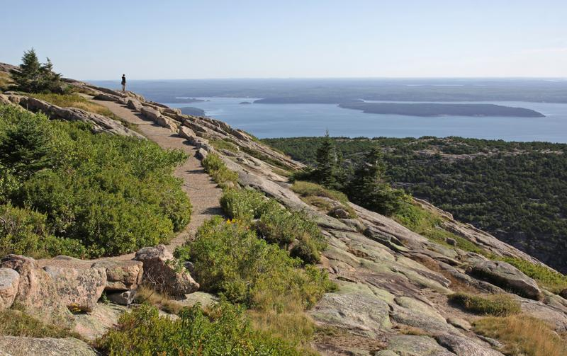 A person enjoying the view from on top of Cadillac Mountain. Located on Mount Desert Island - Acadia National Park, Maine, USA.