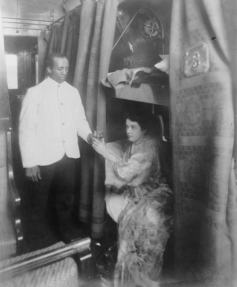 Porter handing young woman a glass of water in railroad sleeping car circa 1905.