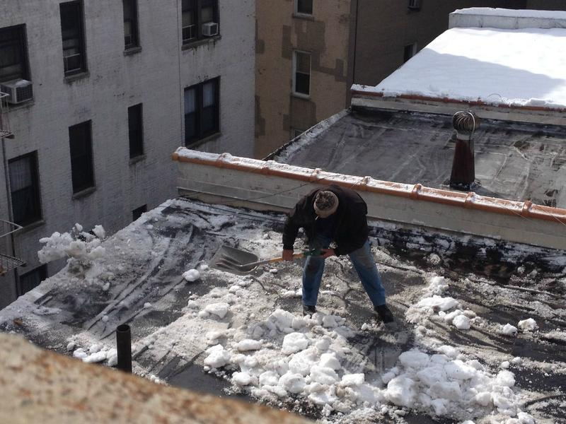 A man removes snow and ice from a roof in Inwood