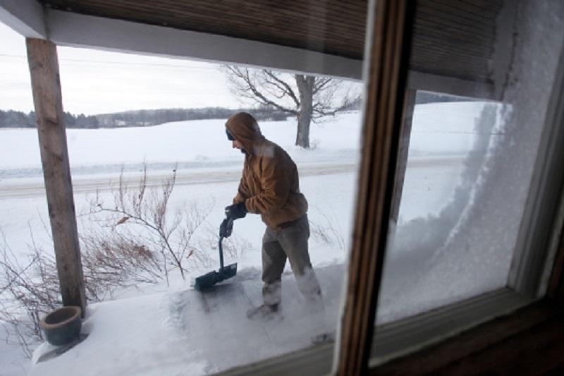 Man, 30 years old, shoveling snow off his porch, Cooperstown, New York.
