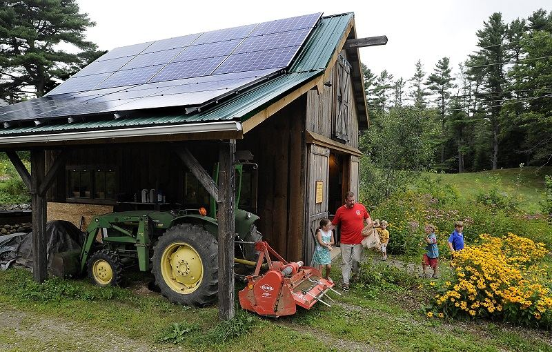 Solar panels cover the roof of the farm stand at Little Ridge Farm as Nick Craney of Bath leaves with his children and their allotment of vegetables from a partnership program.
