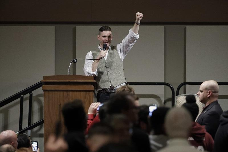 Richard Spencer, who leads a movement that mixes racism, white nationalism and populism, raises his fist as he speaks Tuesday, Dec. 6, 2016, in College Station, Texas.