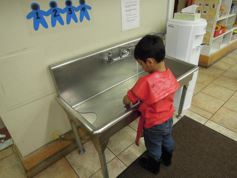 A pre-k student plays at the water station at Goddard Riverside Community Center.