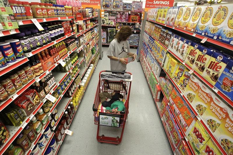 In this Dec. 14, 2010, file photo, Alicia Ortiz shops through the cereal aisle as her daughter Aaliyah Garcia catches a short nap in the shopping cart at a Family Dollar store in Waco, Texas.