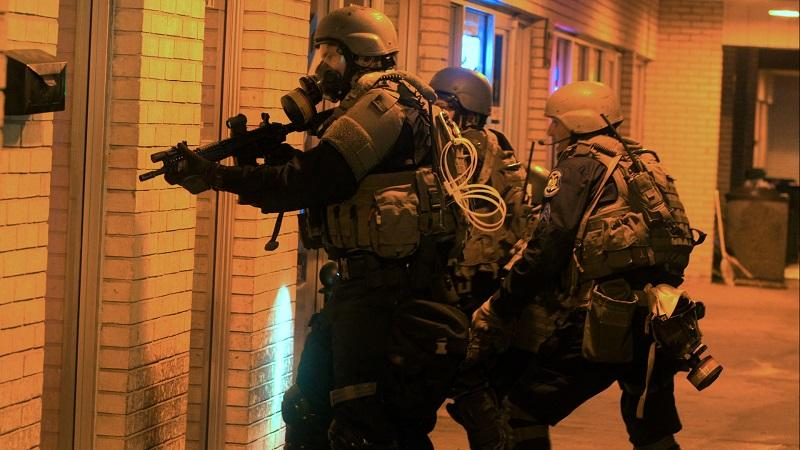 "A swat team at a home in a scene from Craig Atkinson's ""Do Not Resist."""