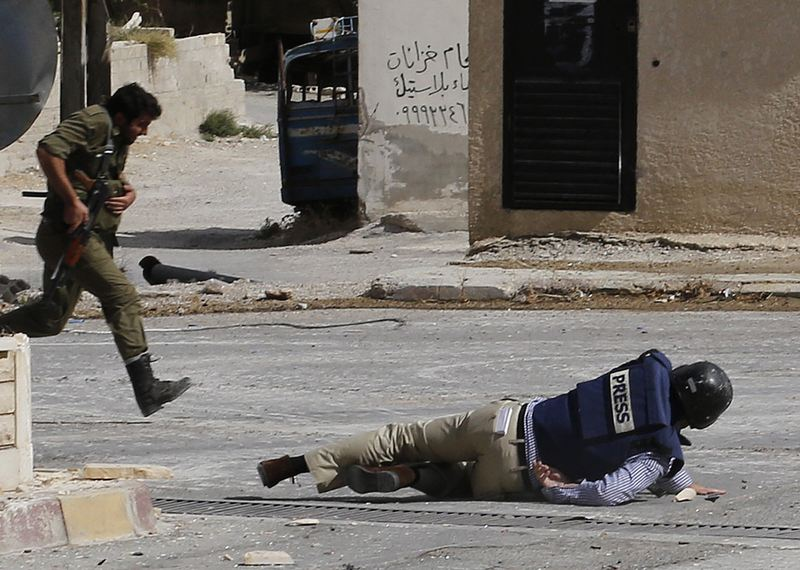 AFP reporter Sammy Ketz hits the ground as a Syrian soldier runs past during sniper fire in the ancient christian Syrian town of Maalula, on September 18, 2013.