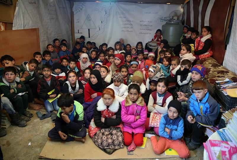 In this Wednesday, Jan. 27, 2016 file photo, Syrian refugee children sit on the ground as they listen to their teacher inside a tent, home for a refugee family that has been turned into a school.