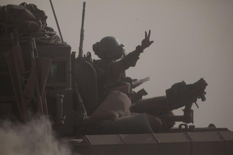 An Israeli soldier flashes the V-sign for 'Victory' on a tank seen moving along the border with Gaza on July 17, 2014 on Israel's border with the Gaza Strip.