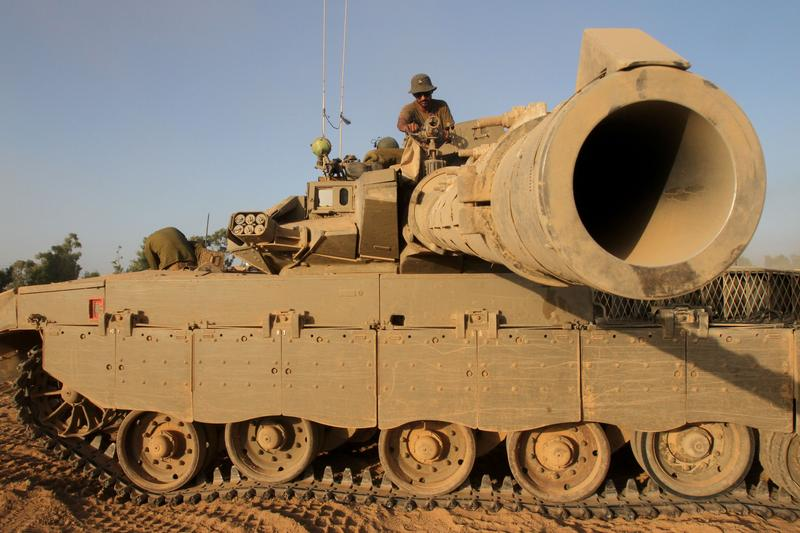 An Israeli soldier sits on top of a Merkava tank along the border between Israel and the Hamas-controlled Gaza Strip, on July 30, 2014, after returning from combat in the Palestinian enclave.