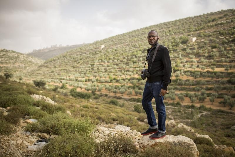 Nigerian-American author Teju Cole walks in terraced hills outside Ramallah during the 2014 Palestine Festival of Literature on June 5, 2014 in Ramallah, West Bank.