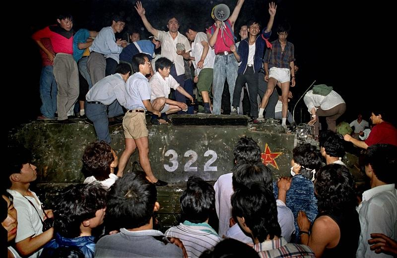 6/4/1989: Civilians with rocks stand on a government armored vehicle near Chang'an Boulevard in Beijing as violence escalated between pro-democracy protesters and Chinese troops, leaving hundreds dead