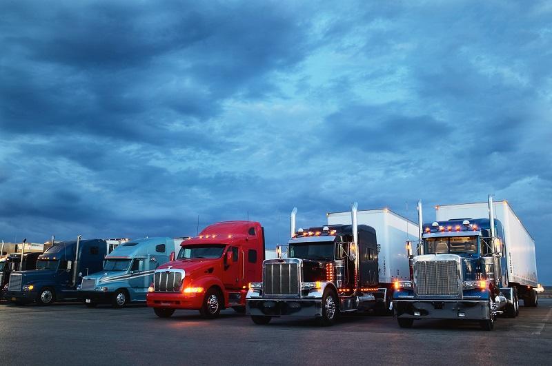 Semi-trucks parked at truck stop, dawn.