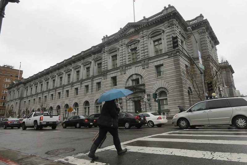 A woman crosses the street outside of the 9th U.S. Circuit Court of Appeals in San Francisco.