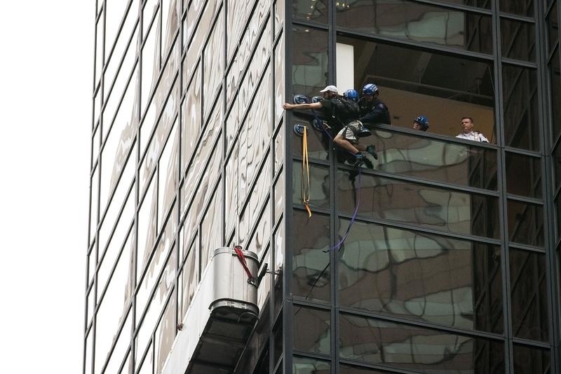 A man identified as 'Steve from Virginia' is grabbed by police as he climbs up the Trump Tower on August 10, 2016 in New York City.