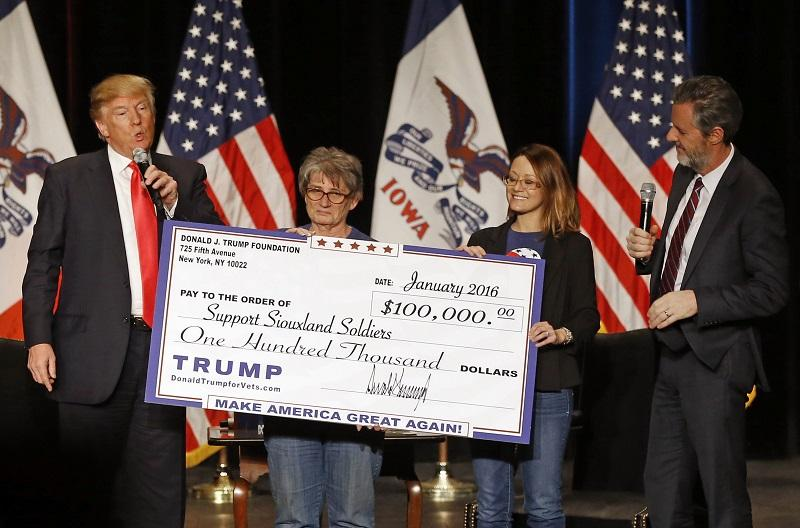 In this Jan. 31, 2016 file photo, Republican presidential candidate Donald Trump, left, presents a check to members of Support Siouxland Soldiers during a campaign event at the Orpheum Theatre in Siou