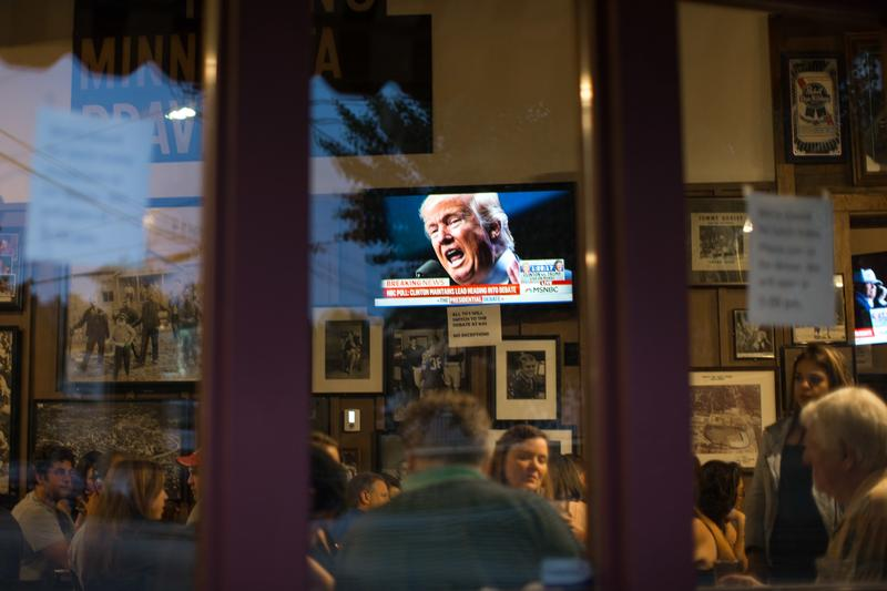 Donald Trump is displayed on a television as patrons wait to watch the first presidential debate between Trump and Hillary Clinton.