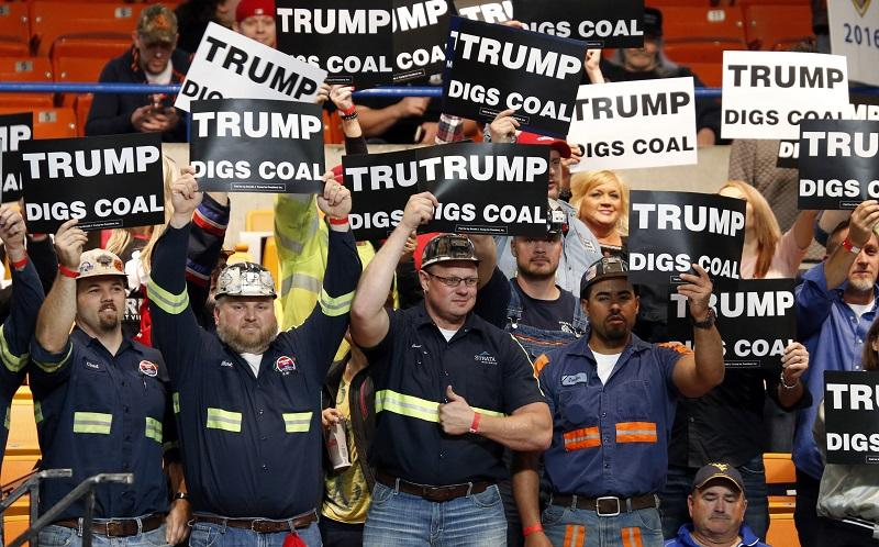A group of coal miners wave signs for Republican presidential candidate Donald Trump as they wait for a rally in Charleston, W.Va., Thursday, May 5, 2016.