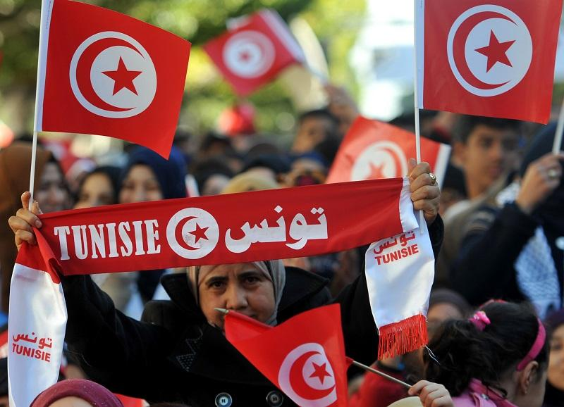 A woman holds her national flag during a rally on January 14, 2016 in the Habib Bourguiba Avenue in the capital Tunis to mark the fifth anniversary of the 2011 revolution.