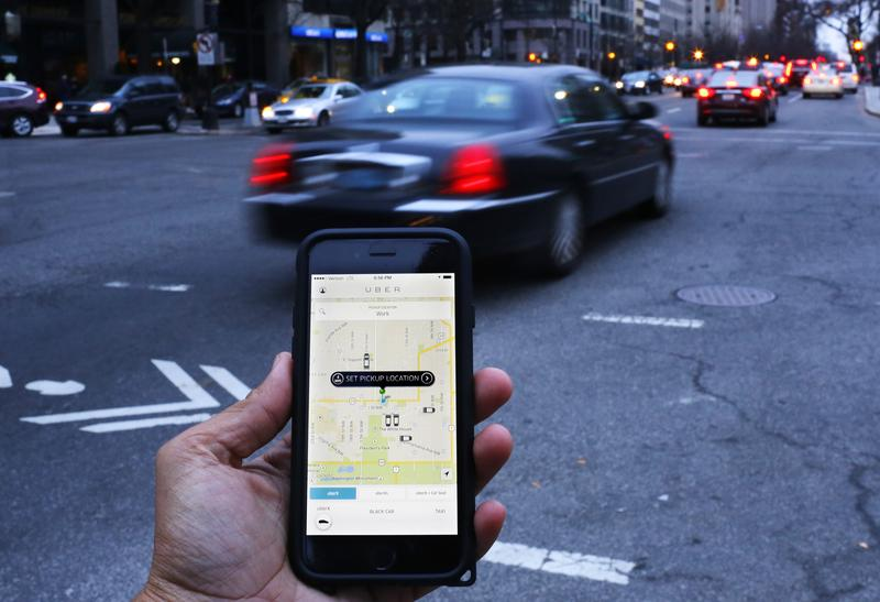An UBER application is shown as cars drive by in Washington, DC on March 25, 2015.
