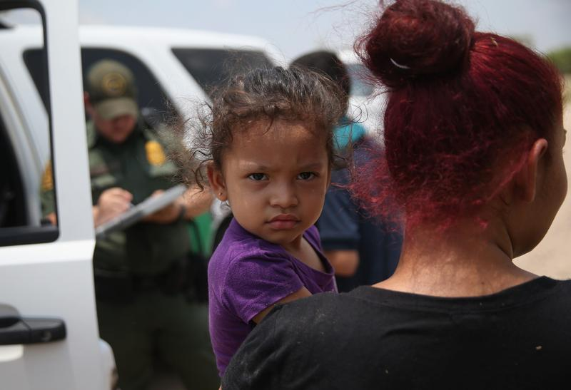 July, 24, 2014 A mother and child, 3, from El Salvador await transport to a processing center for undocumented immigrants after they crossed the Rio Grande into the United States in Mission, Texas