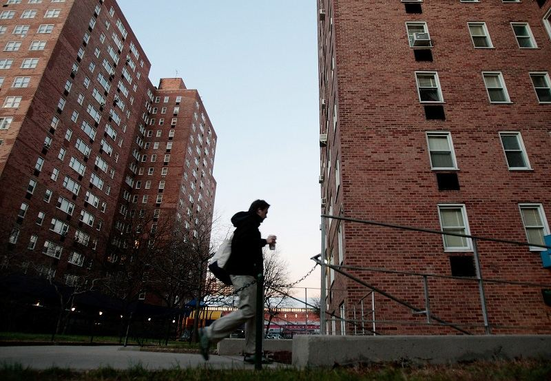 A man walks into the Savoy Park apartment complex on December 3, 2008 in Harlem, New York.