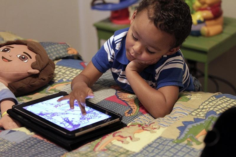 In this Friday, Oct. 21, 2011 photo, Frankie Thevenot, 3, plays with an iPad in his bedroom at his home in Metairie, La.