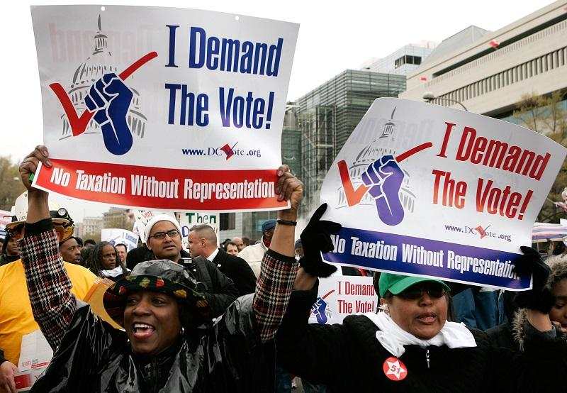 Demonstrators hold posters during a march to ask for a voting representation for the nation's capital in the U.S. House of Representatives April 16, 2007 in Washington, DC.
