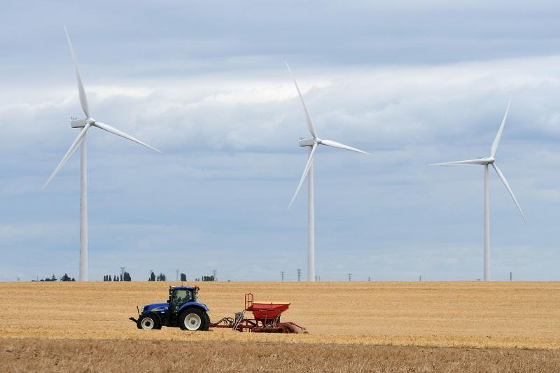 A farmer passes next to wind turbines on a wind farm in Guillonville, central France, on August 18, 2016.