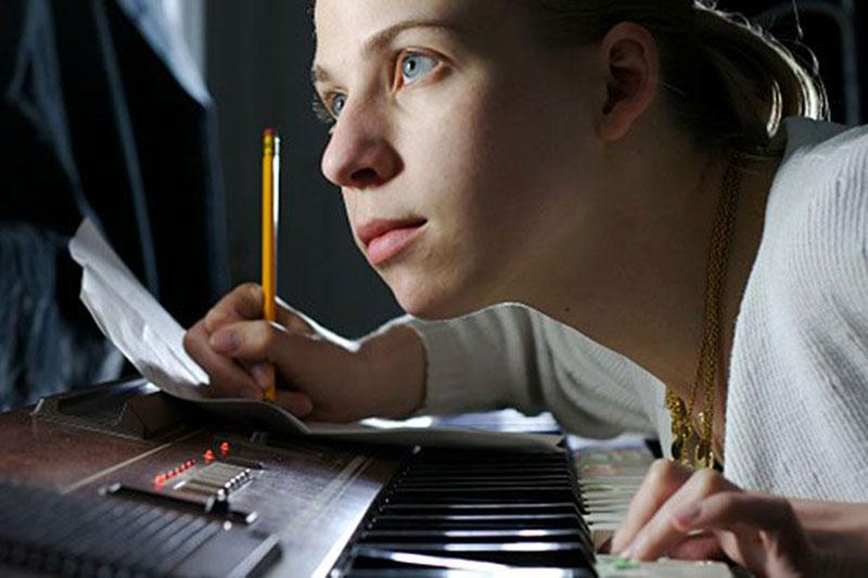 Young Woman Writing Music and Playing Piano