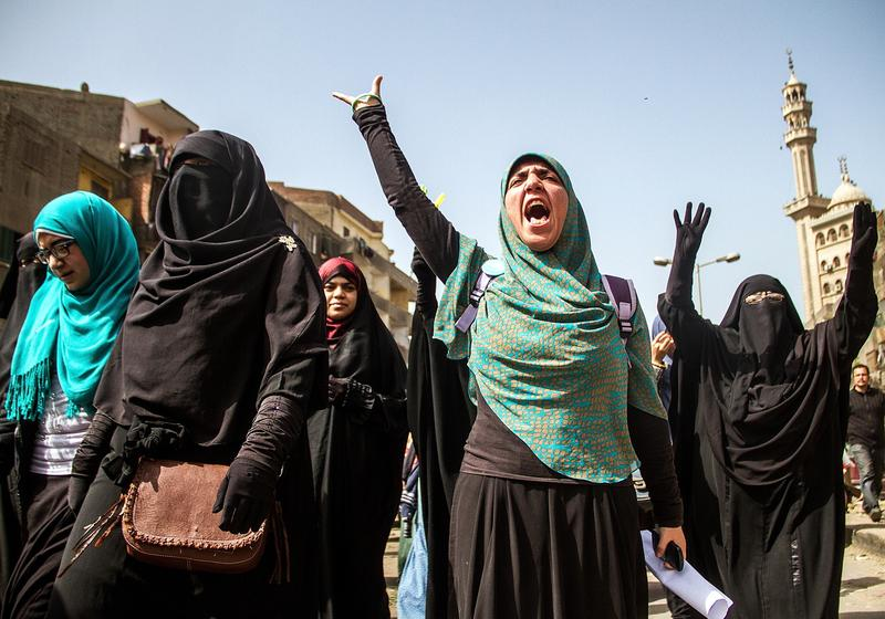 Women flash Rabia sign as Egyptians who call themselves as 'Anti-Coup demonstrators' stage a demonstration in the Al-Matariyyah district of Cairo, Egypt on February 27, 2015.
