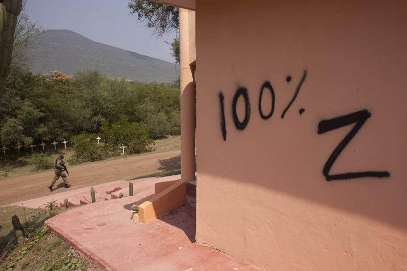 """In this Oct. 24, 2012 photo, a soldier patrols near a temple allegedly built by the drug cartel """"Caballeros Templarios,"""" or Knights Templar, that shows signs of vandalism allegedly left by the Zetas."""
