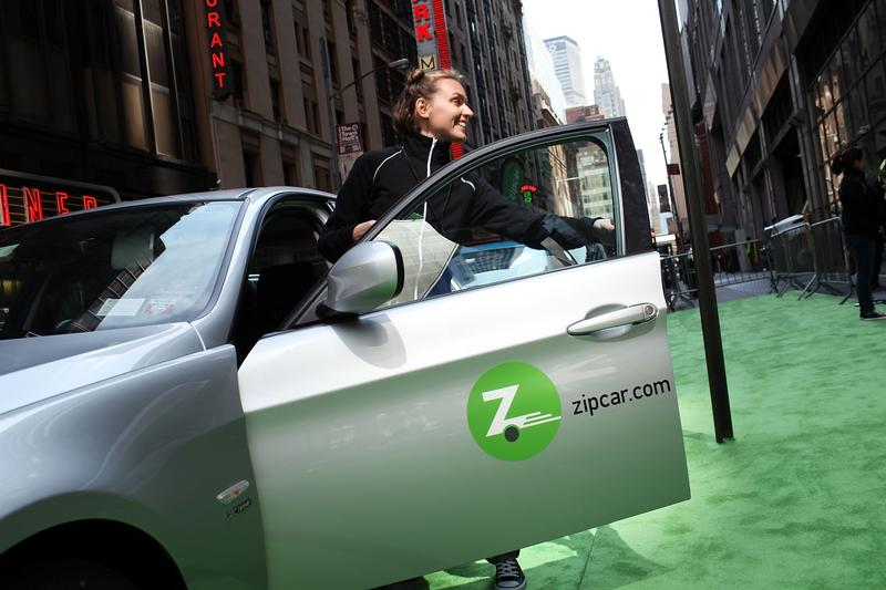 A woman demonstrates how to register into a Zipcar during a promotion of the short term car rental company on April 14, 2011 in Times Square in New York City.