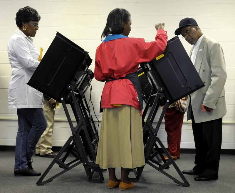 A voter gets directions on how to use the electronic voting booth at the Board of Elections early voting site on October 18, 2012 in Wilson, North Carolina.