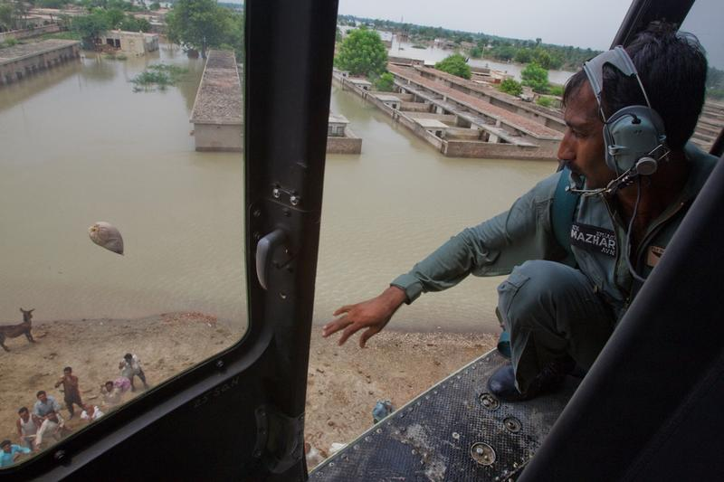 A Pakistan Army soldier throws food to flood victims during air rescue and relief operations on August 9, 2010 near to Kot Addu in the Muzaffargarh district in Punjab, Pakistan.