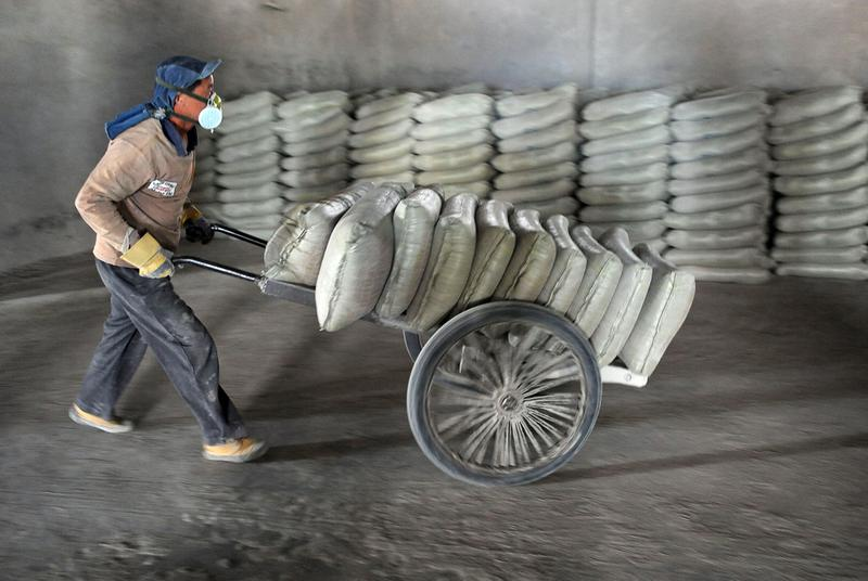 A Chinese worker wears a mask as he delivers bags of cement at a factory in Hefei, east China's Anhui province on October 6, 2010.