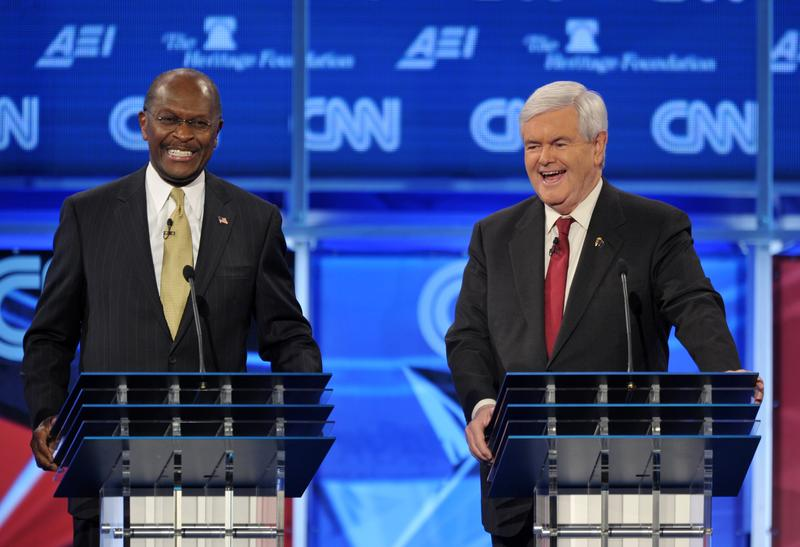 Former House speaker Newt Gingrich and former pizza executive Herman Cain laugh following an exchange during a Republican presidential debate on November 22, 2011.