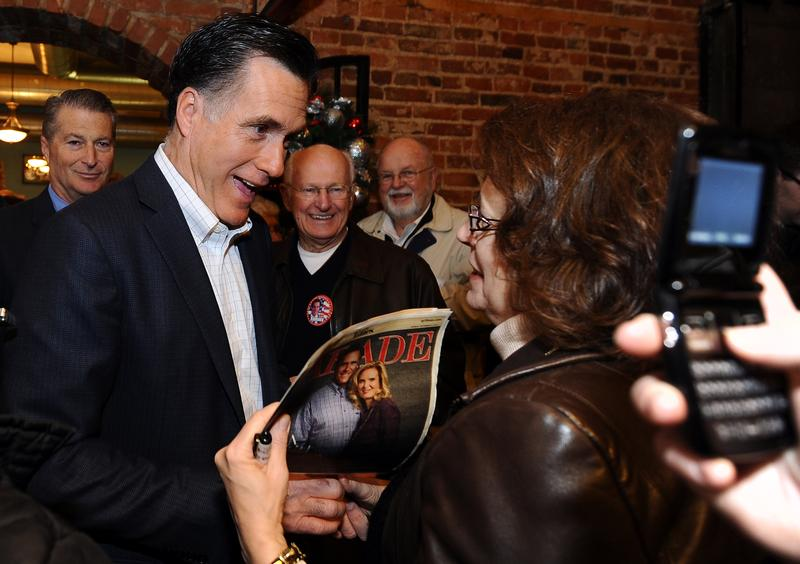 Mitt Romney signs autographs for a supporter during a campaign stop in Muscatine, Iowa.