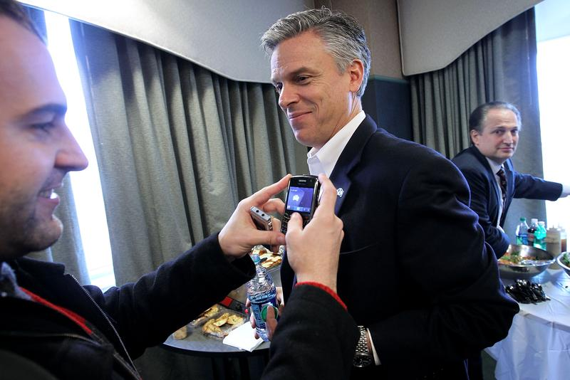 A local business owner photographs Jon Huntsman's lapel pin after a speech in Portsmouth, New Hampshire.