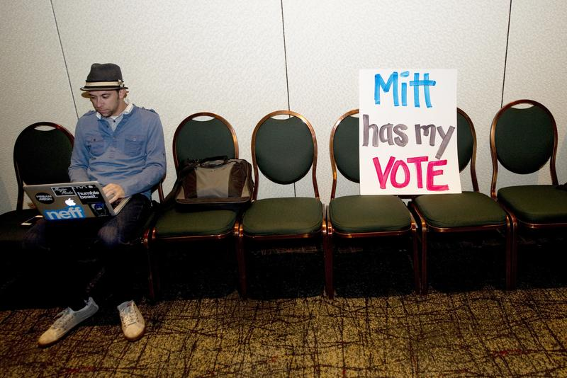 A supporter of Mitt Romney watches polling results on his at his victory party in Arizona.